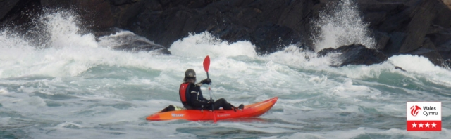 Outdoor activities including kayaks, coasteering, climbing in Pembrokeshire