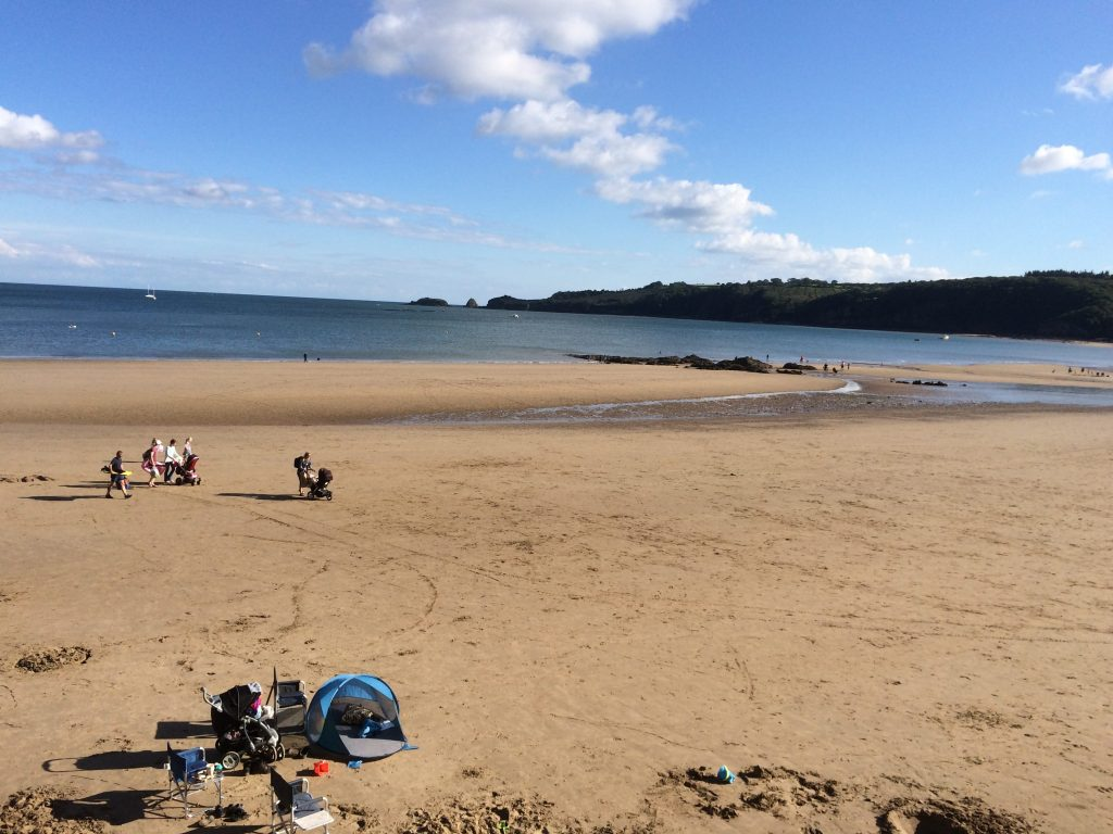 View of Saundersfoot beach with families enjoying the quiet wide open golden sand