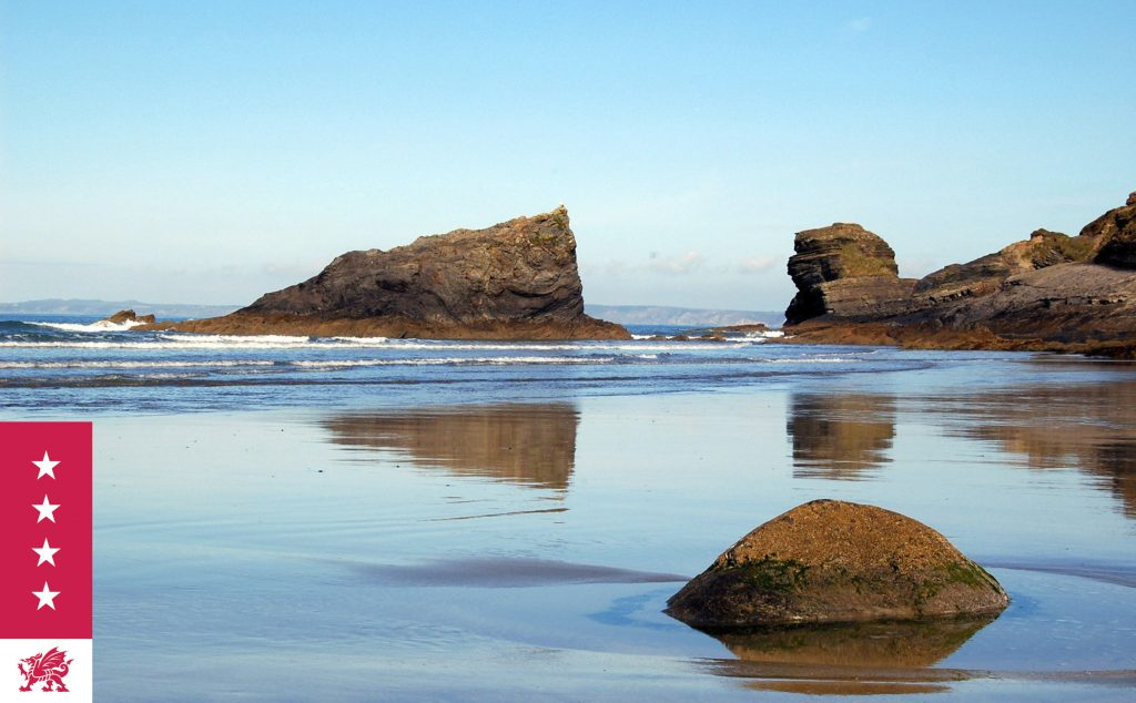 Coastal scene with rock formations reflected on a wet beach